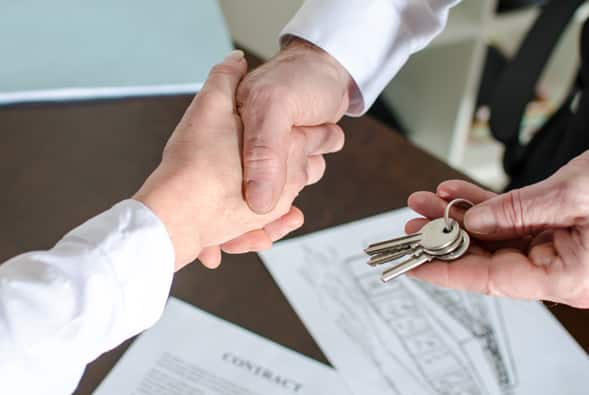 An image of two people shaking hands and the trading of keys